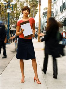 Woman Standing on Street with Clipboard
