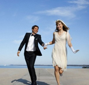 Newlyweds running on a beach
