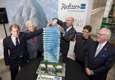 Thorsten Kirschke, president, Carlson Hotels Americas performs the ceremonial groundbreaking of the Radisson Blu Aqua Hotel, Chicago with the first cut of the 4 foot tall Aqua Tower replica cake
