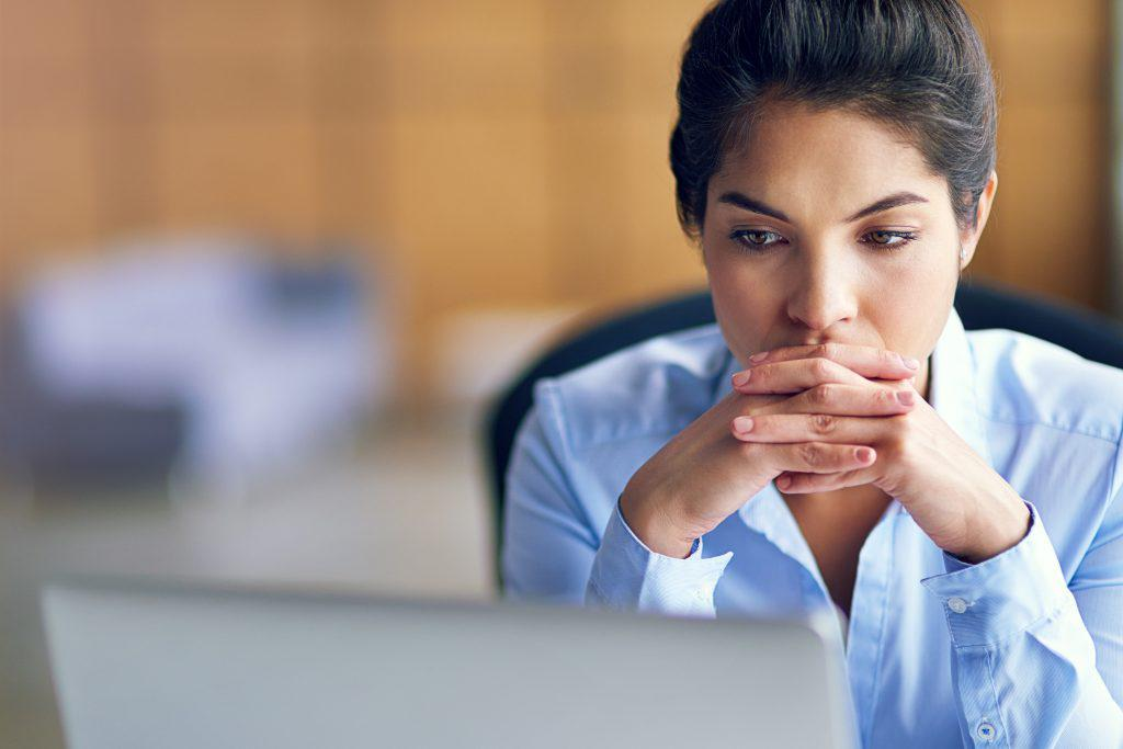 Shot of a young businesswoman looking stressed while working on her laptop