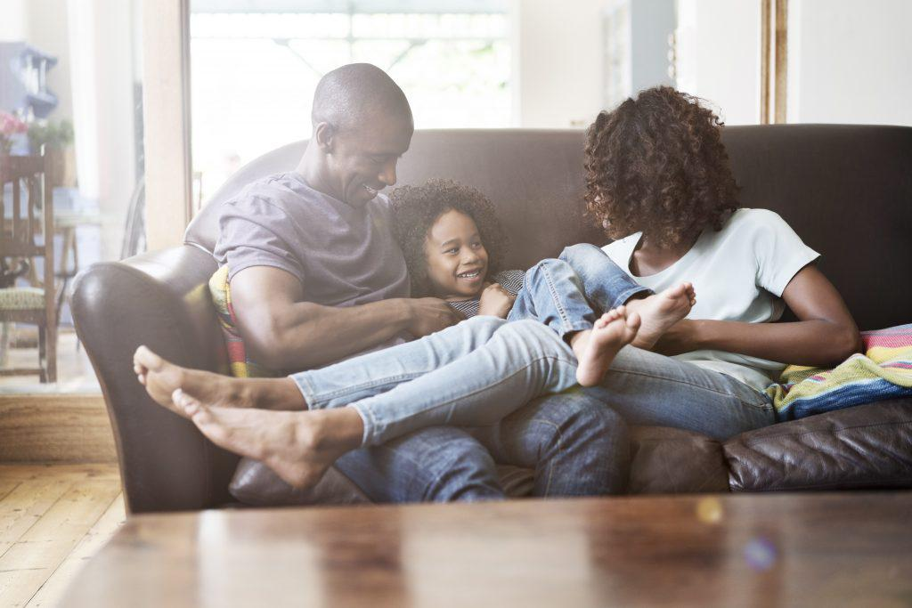 A photo of cheerful family sitting on sofa at brightly lit home. Happy parents are playing with son in living room. They are in casuals.